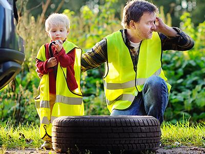 Kind und Mann in Warnweste stehen am Straßenrand mit Reifenpanne