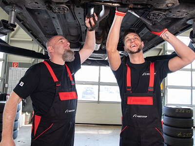 Zwei First Stop KFZ Mechaniker schrauben am Unterboden eines Fahrzeugs