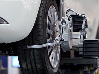 Am Fahrzeug wird der Winkel des Rades zur senkrechten Achse und die parallele Laufrichtung ausgemessen.