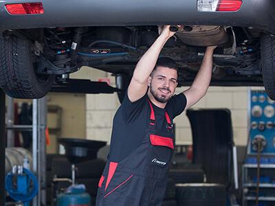 Kfz-Mechatroniker untersucht die Auspuffanlage des Fahrzeugs
