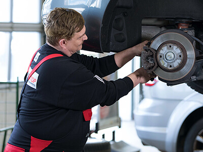 Kfz-Meister wechselt Bremsbeläge am Fahrzeug