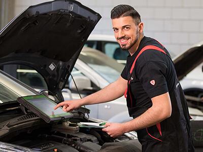 Kfz-Mechatroniker liest mit Hilfe eines Diagnosegerätes den Fehlerspeicher des Autos aus.