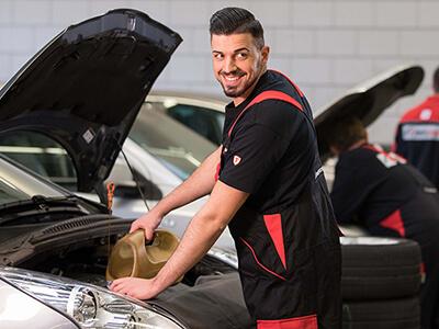 First Stop Mitarbeiter füllt Öl nach