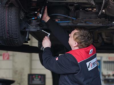 Kfz-Meister kontrolliert Stoßdämpfer am Fahrzeug