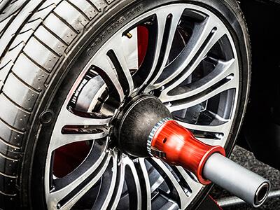 Reifen wird an Reifenwuchtmaschine gewuchtet