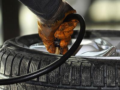 Werkstattmitarbeiter befüllt Reifen mit Reifengas