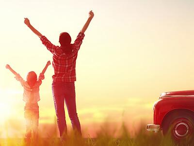 Kind und Frau jubeln der Sonne entgegen, daneben steht ein roter Oldtimer