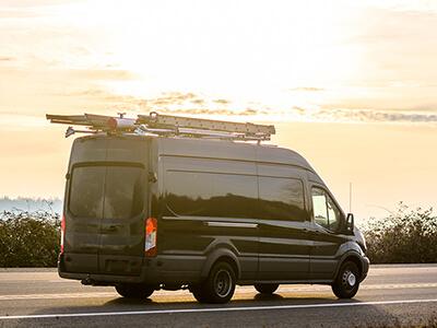 Schwarzer Transporter mit Werkzeug auf dem Dach fährt in den Sonnenuntergang