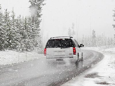 SUV fährt bei Schneefall auf schneebedeckter Straße mit eingeschränkter Sicht
