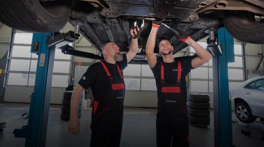 Zwei First Stop Mitarbeiter schrauben an Unterseite eines Autos