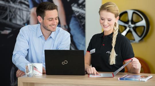 Frau und Mann hinter Laptop im Verkaufsgespräch